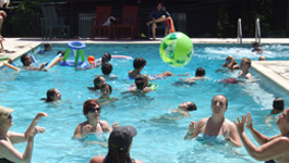 Adults and children enjoying swimming pool.
